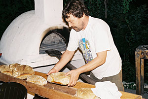 Spyros baking bread in our wood oven - click to enlarge